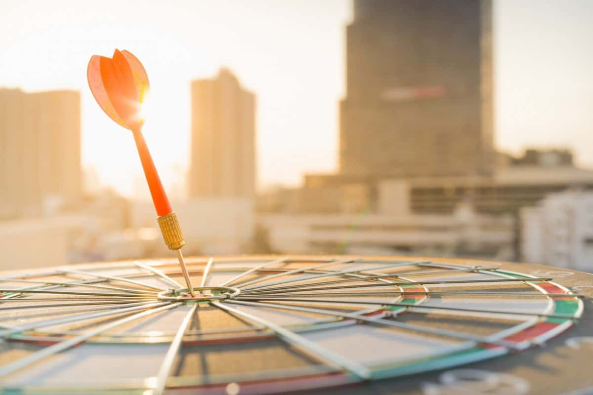 Dart on Dartboard with Cityscape in the Background
