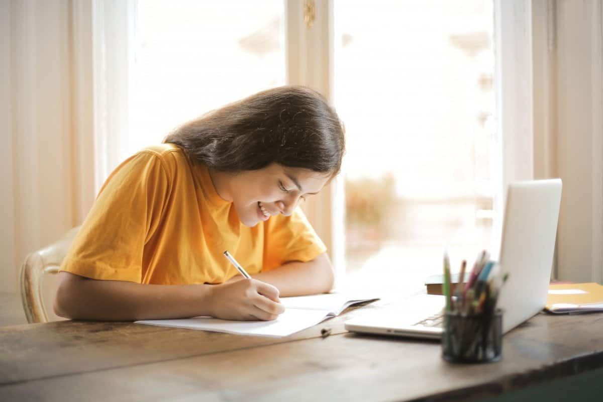 Girl Writing in Workbook from Online Course with Laptop on Desk