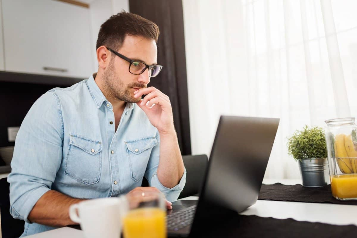 Man with Glasses Watching Online Course on His Laptop with Orange Juice on Desk