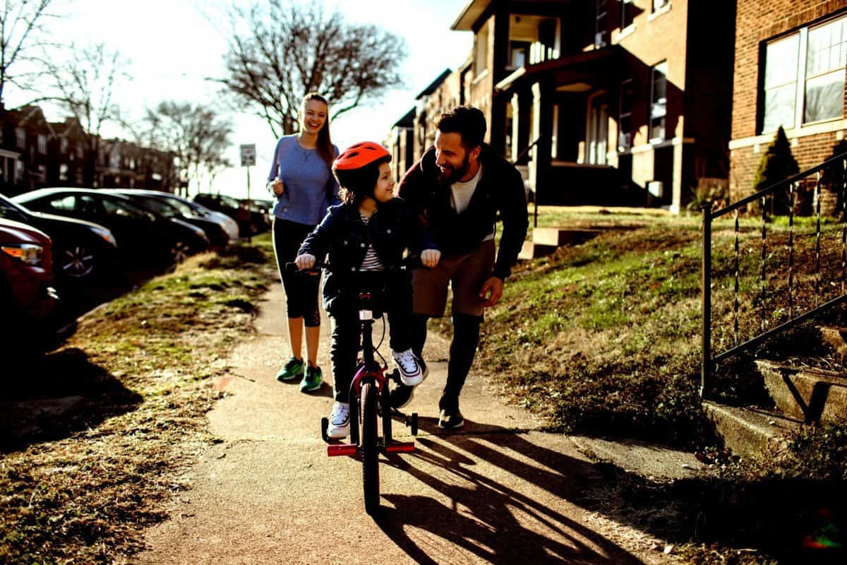 Mother and Father Outside with Daughter Riding a Bike
