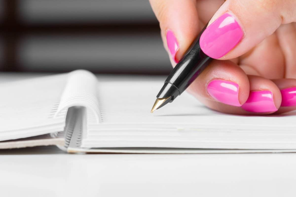 Woman with Pink Fingernails Writing in Notebook with a Pen