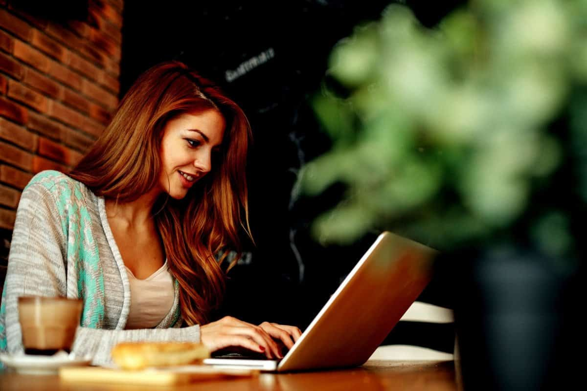 Woman with Red Hair Working on Laptop from Coffee Shop