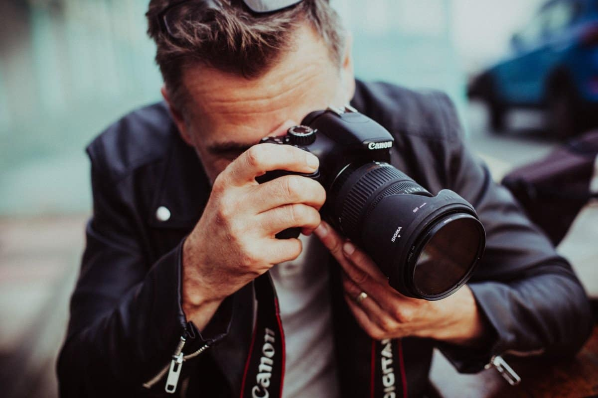 Man Holding a Camera with a Lens Taking Photos