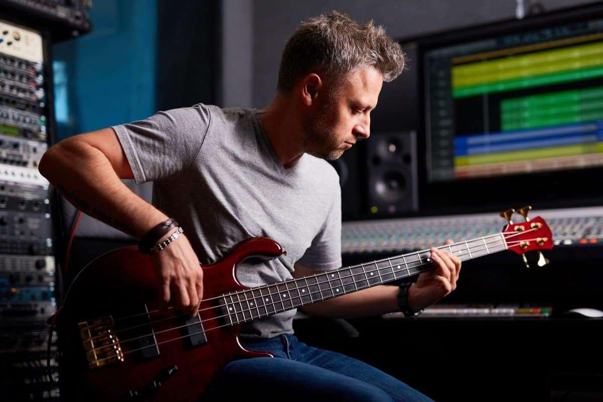 Man Playing Red Bass Guitar in Recording Studio