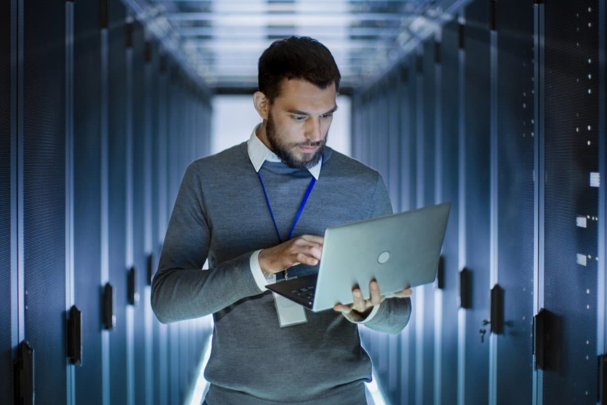 Man Holding Computer in Technology Hallway with Processors