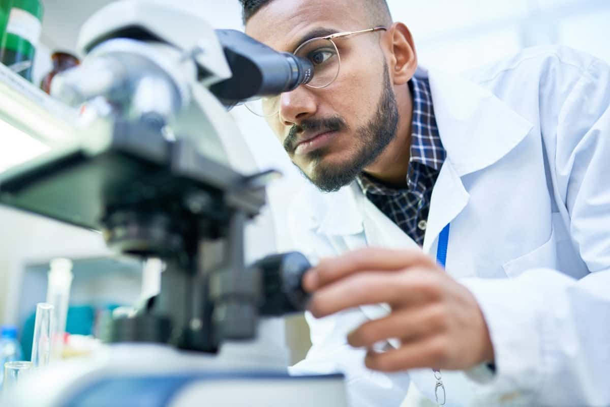 Scientist in Lab Coat Looking through a Microscope
