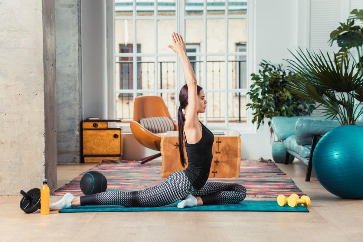 Woman Doing Yoga on Matt in Living Room with Workout Equipment
