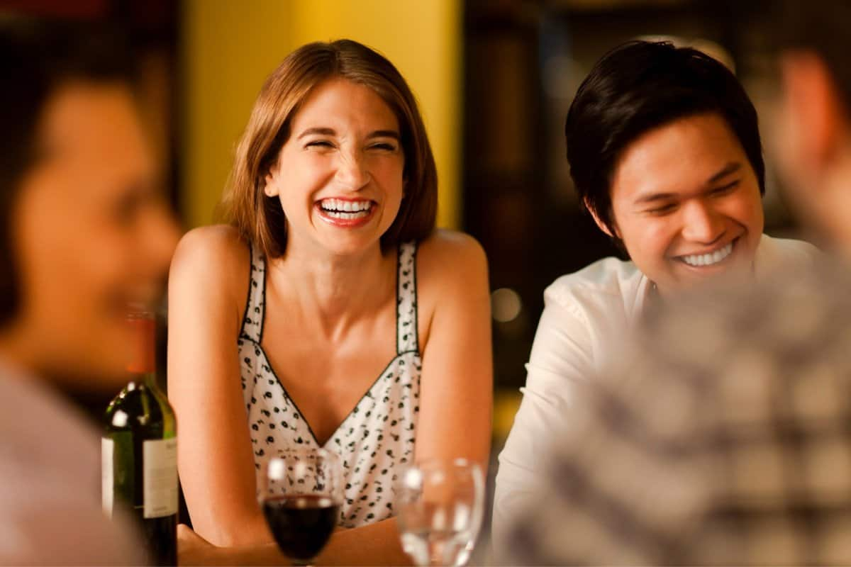 Woman Laughing with Others While Drinking Wine