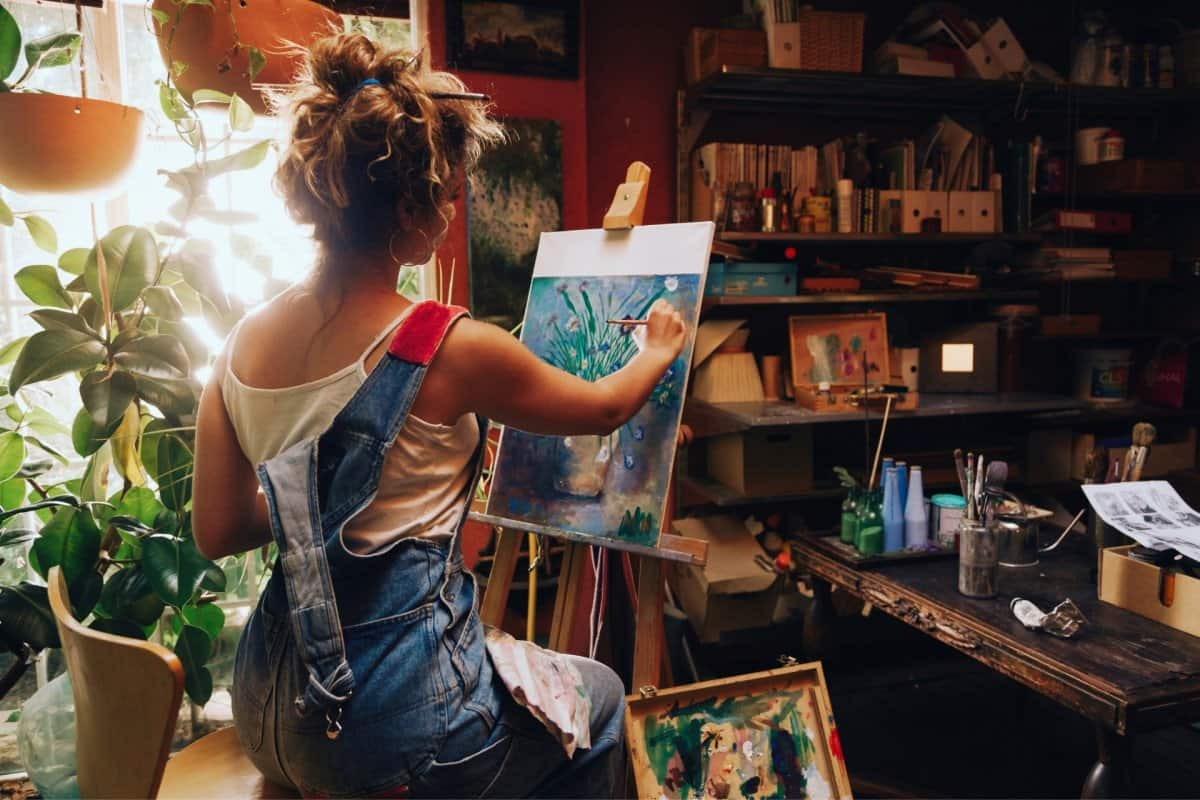 Woman in Overalls Painting on Canvas in Art Room