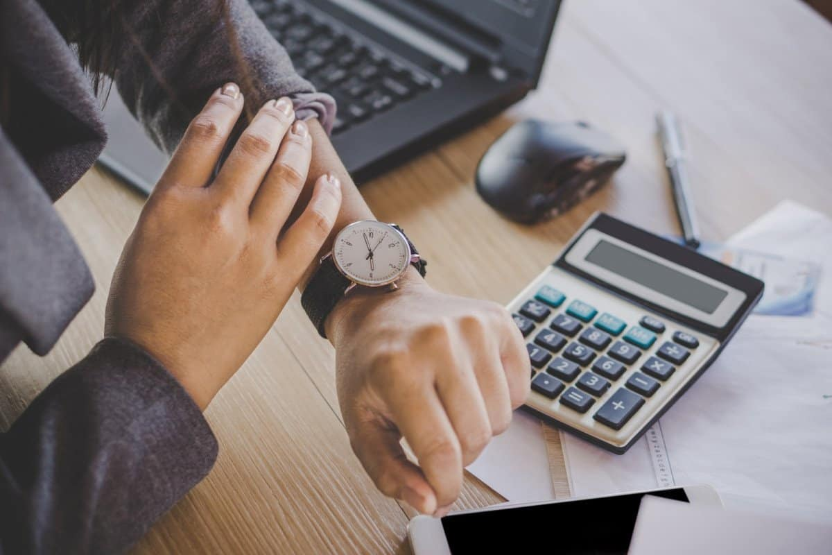 Person with Watch Looking at the Time with Calculator and Desk