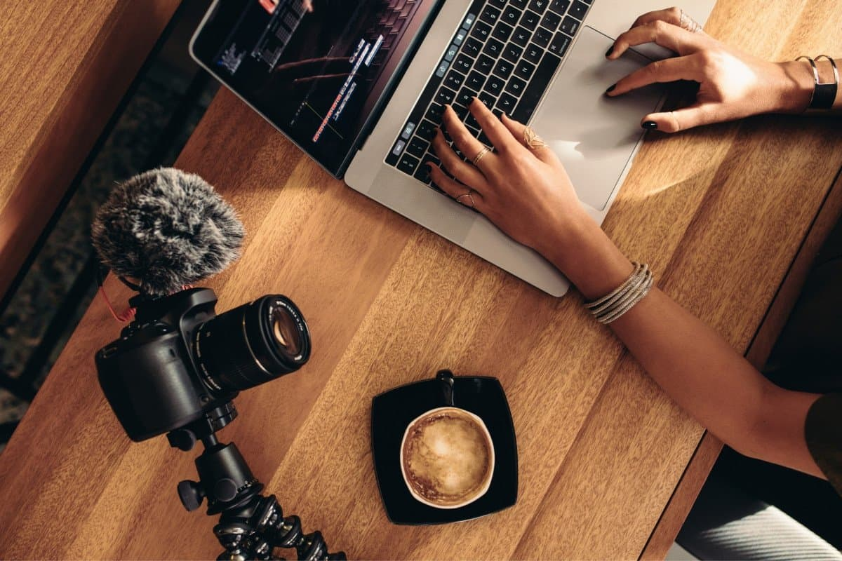 Woman Editing Video on Laptop with DSLR Camera and Coffee on Table