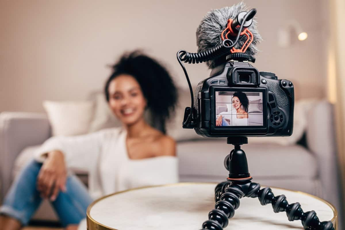 Woman Sitting on Couch with DSLR Camera and Shotgun Microphone