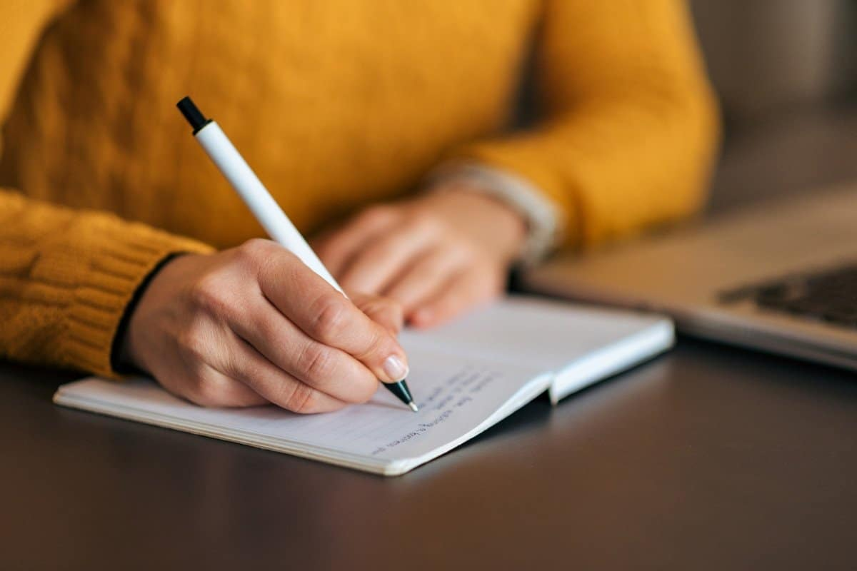 Woman in Yellow Sweater Writing Course Outline in a Notebook