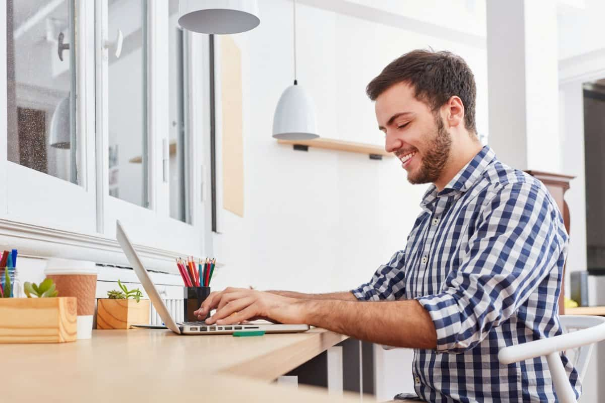 Man Smiling and Sitting at Desk Typing on the Computer