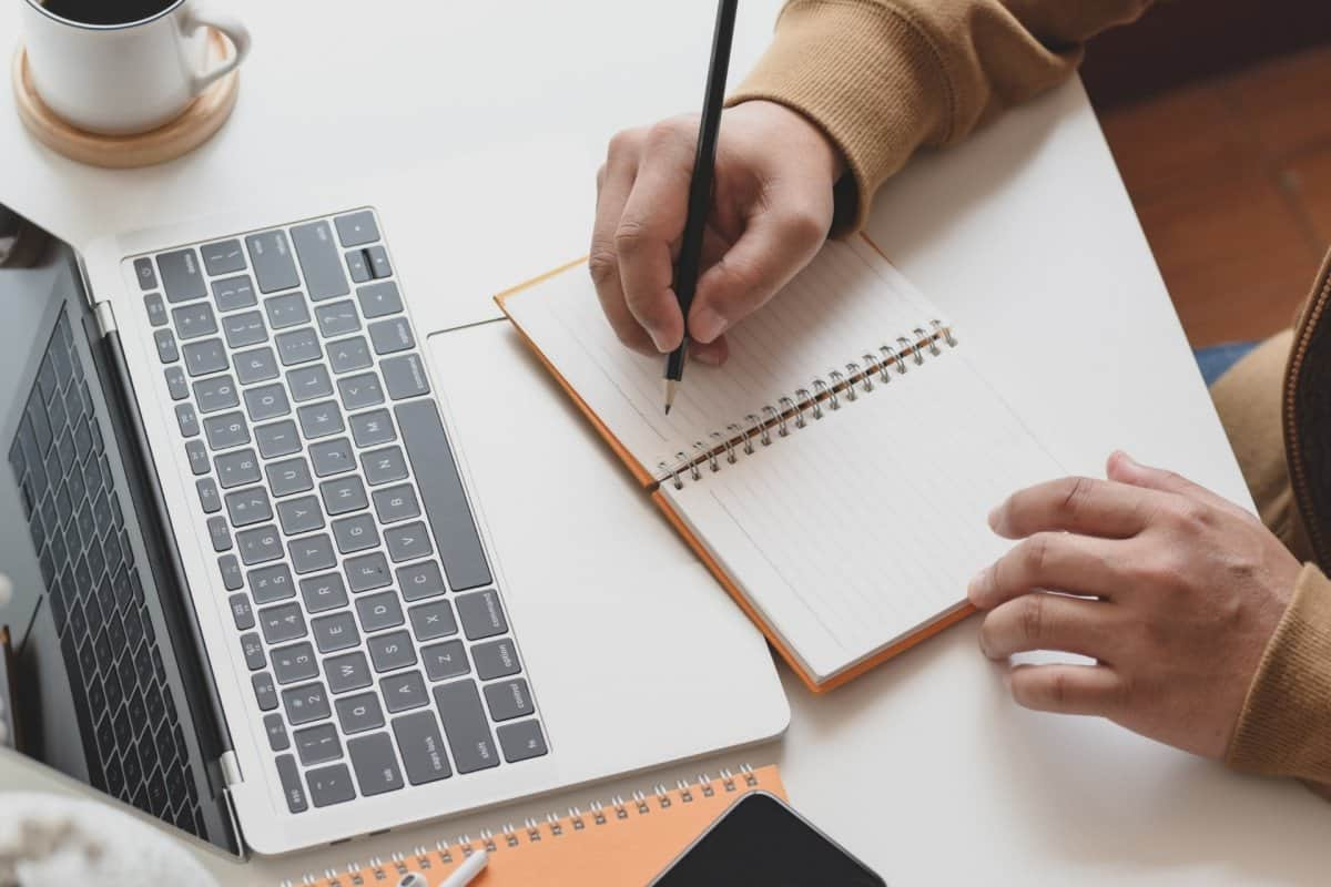 Person Writing in Notebook on Desk with Laptop and Coffee
