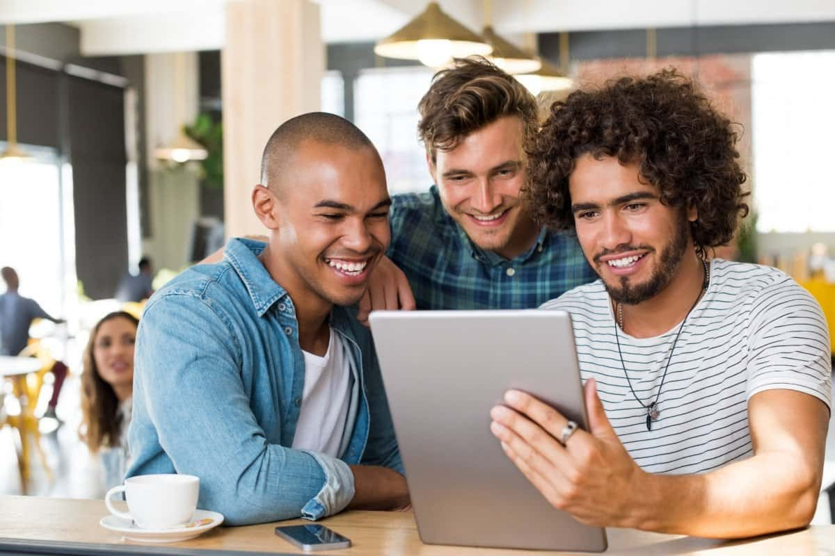 Three Guys Watching Video on a Table in a Coffee Shop