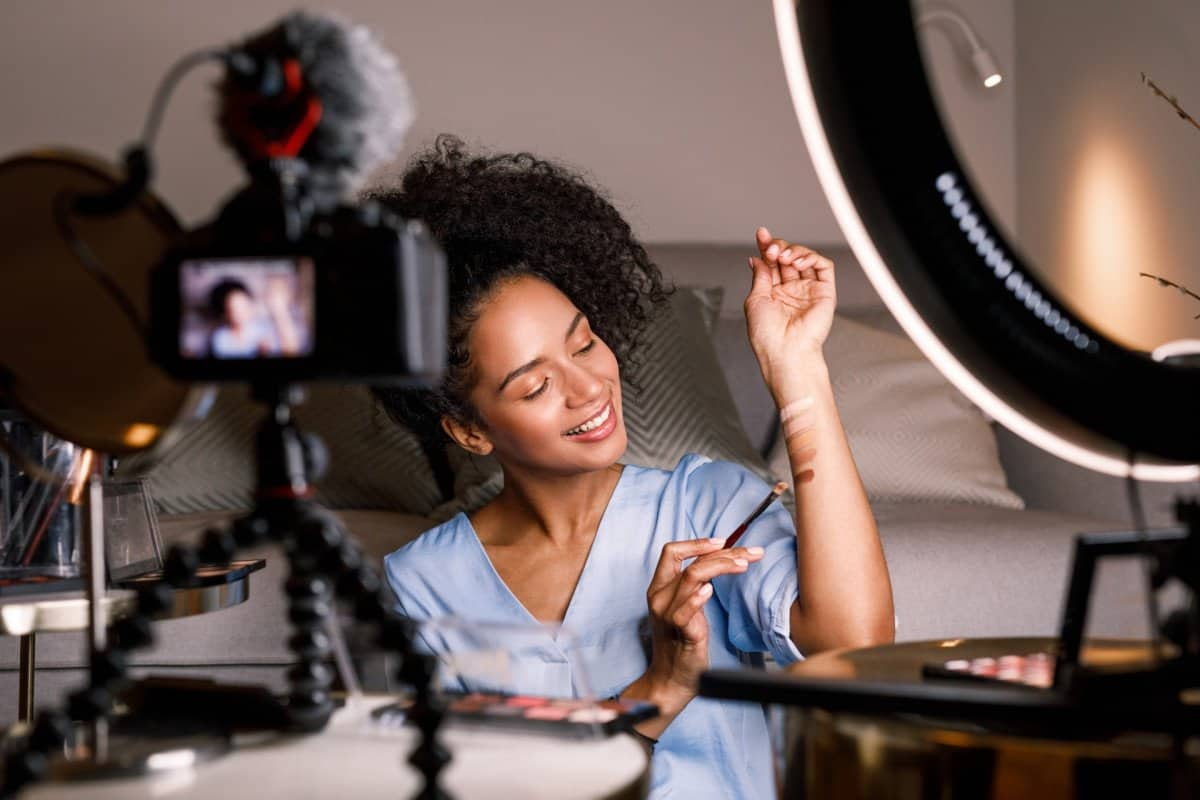 Woman Applying Makeup to Arm while Filming an Online Course