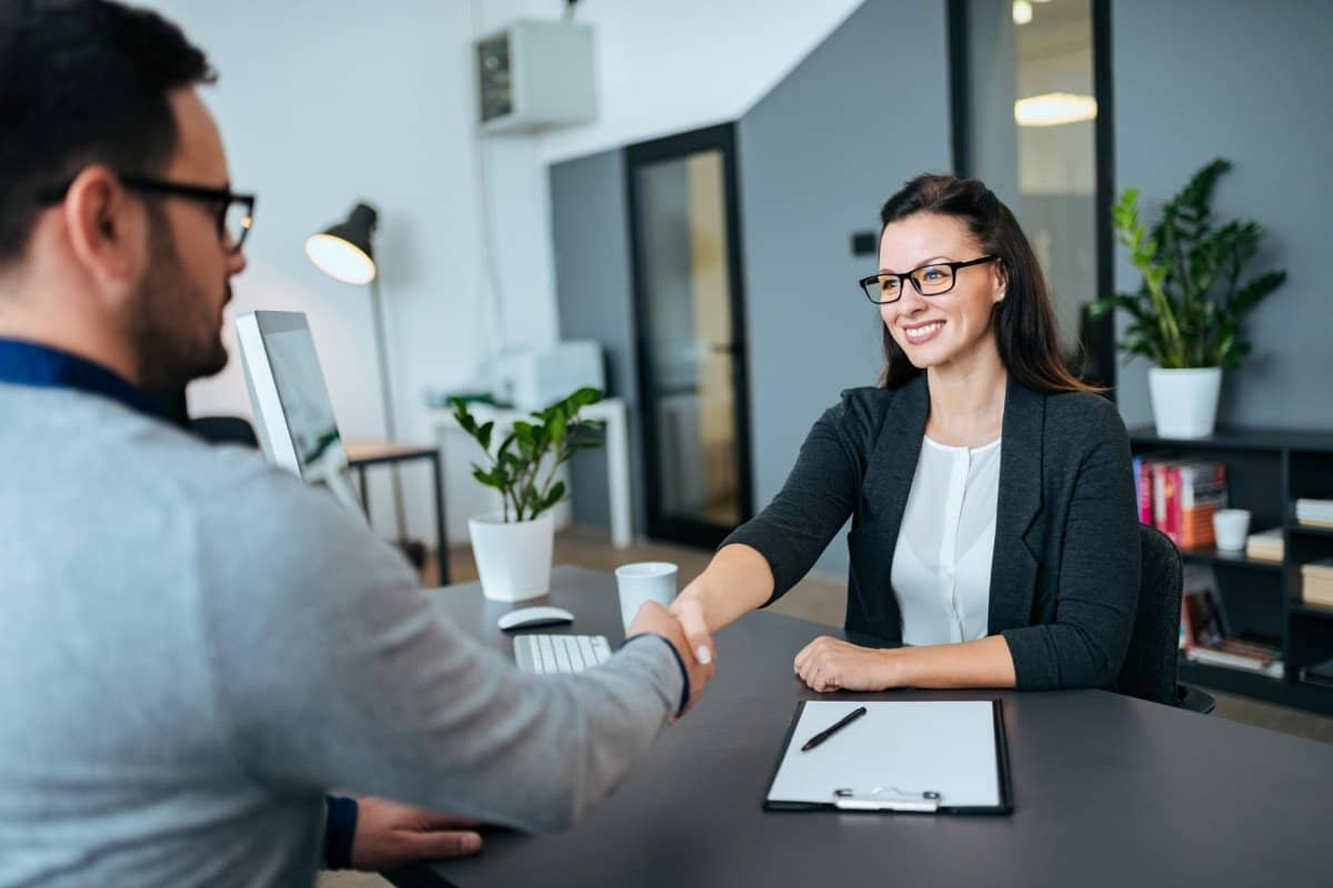 Woman Shaking Mans Hand at a Job Interview