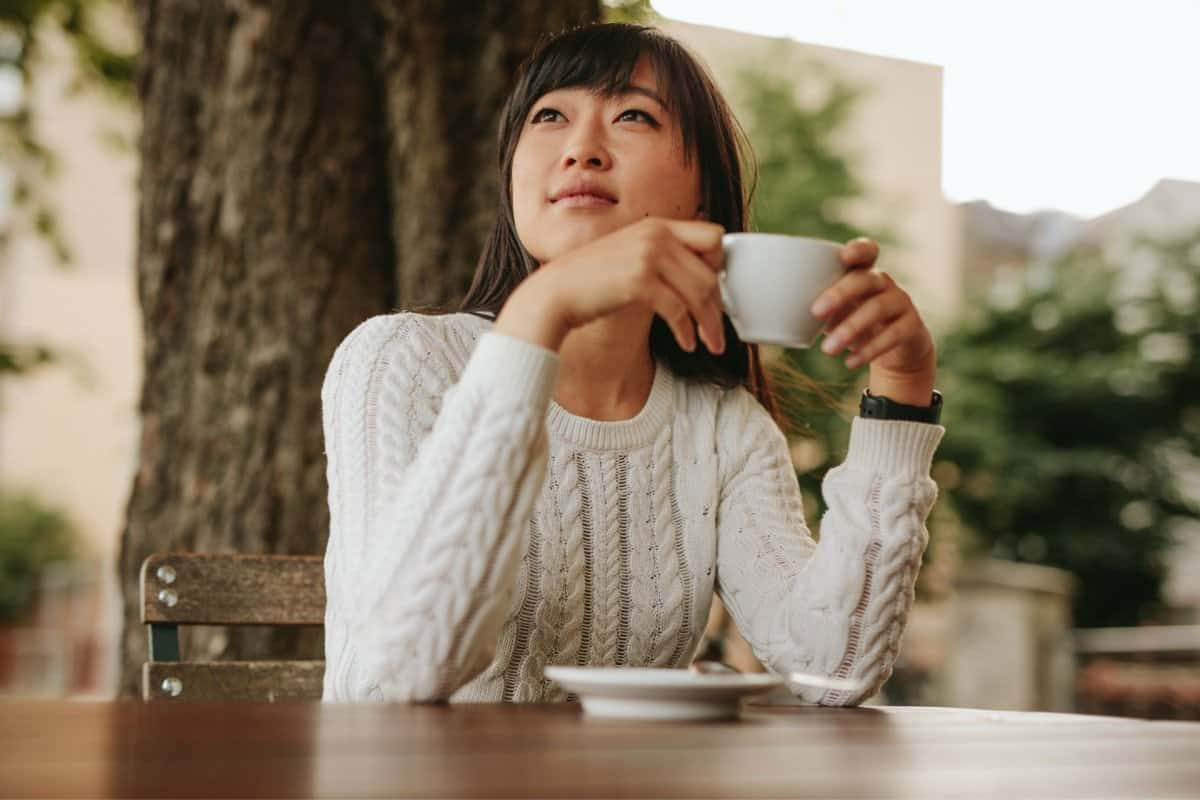 Woman Thinking About an Online Course while Drinking Coffee