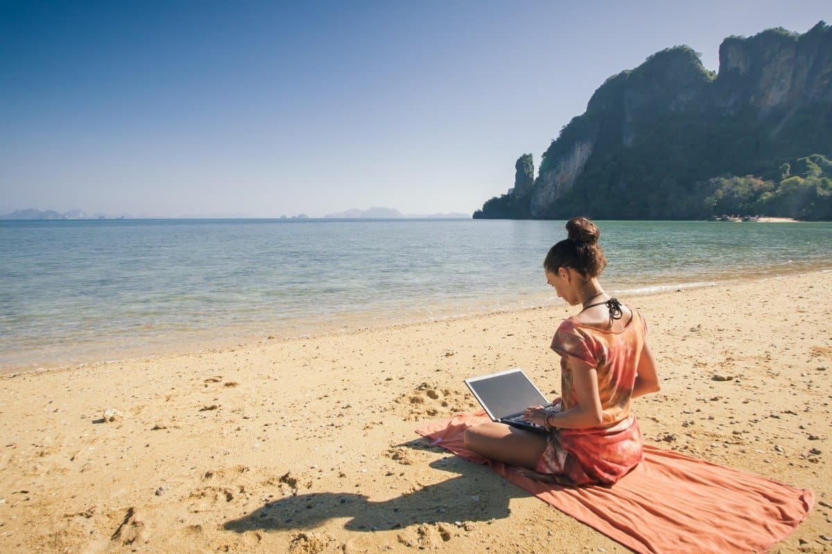 Woman Using Computer on the Beach with Ocean and Mountains in Background