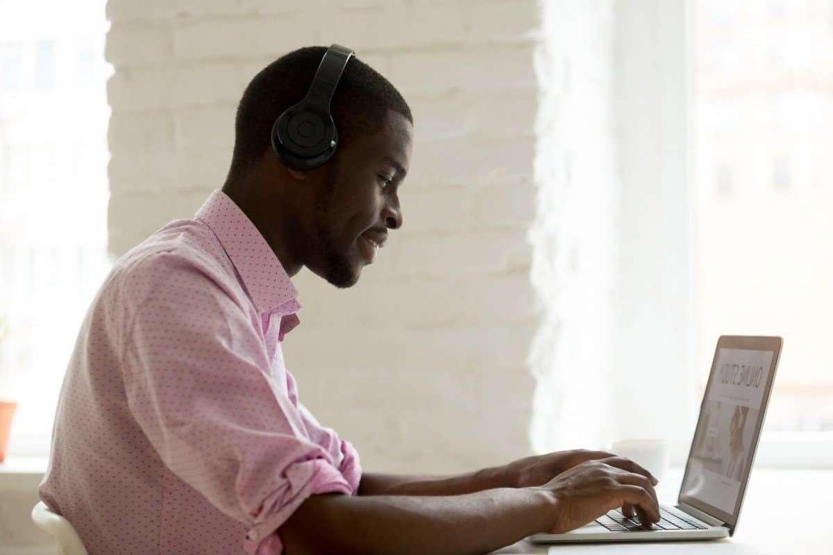 Man in Pink Shirt Typing on Laptop